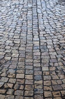 Старая вертикаль текстуры предпосылки улицы булыжника