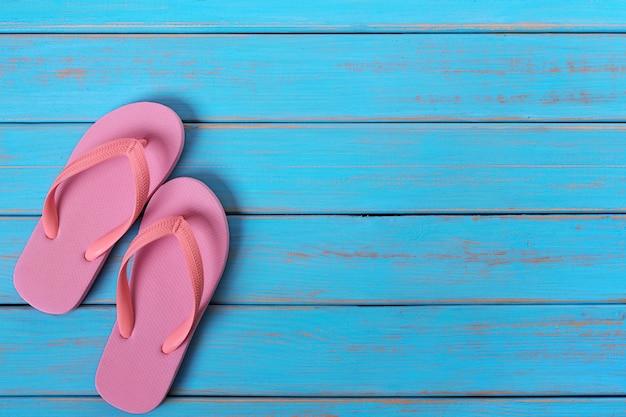 ピンクのフリップフロップサンダル古い夏のビーチウッドの背景を描いた