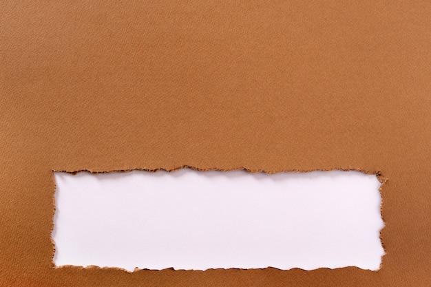引き裂かれた茶色の紙の背景フレームストリップ下端