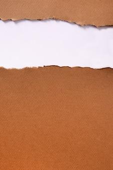 引き裂かれた茶色の紙ストリップヘッダーの背景の垂直