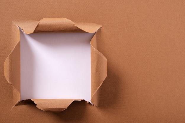 引き裂かれた茶色の紙の正方形の穴の背景フレーム