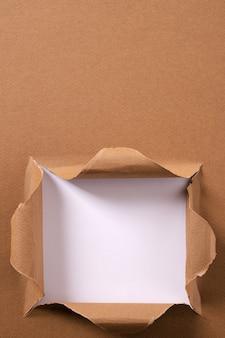 引き裂かれた茶色の紙の正方形の穴の背景フレーム垂直