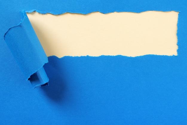 引き裂かれた青い紙ストリップ黄色背景フレーム