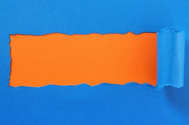引き裂かれた青い紙センターストリップオレンジ色の背景