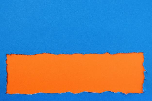 引き裂かれた青い紙ストリップオレンジ色の背景の枠線