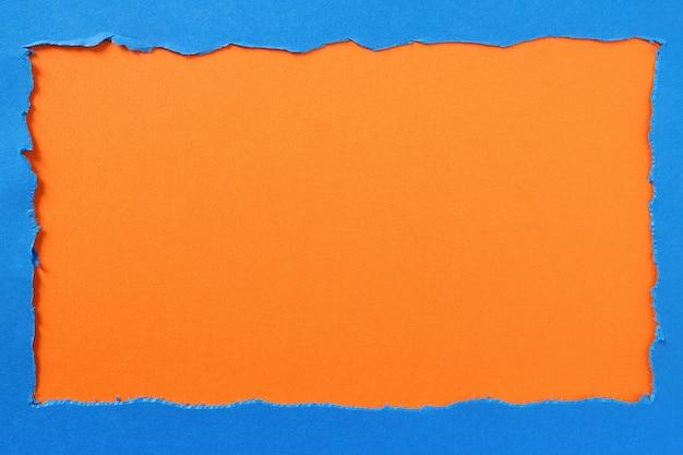 引き裂かれた青い紙オレンジ色の背景の枠線
