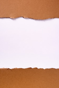引き裂かれた茶色の紙ストリップの背景フレーム垂直
