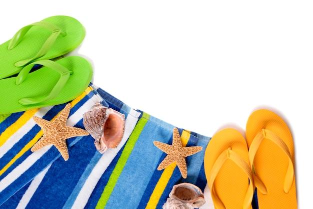 フリップフロップ、ヒトデ、貝殻を白で隔離されるビーチタオル。