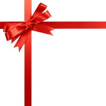 Рамка границы красного смычка ленты подарка вертикальная угловая изолированная на белизне.