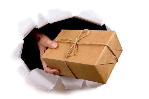 Человек доставки посылки через разорванной фоне