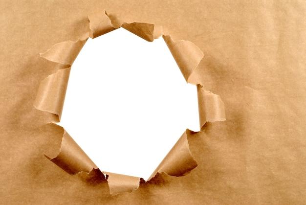 破れた穴と茶色の紙の背景