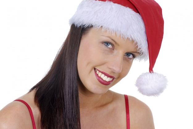 白で隔離赤いクリスマスサンタ帽子と笑顔の若い成人女性のクローズアップ