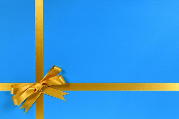 青色の背景にゴールドのギフトリボン弓