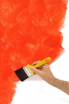 Человек рисует красную стену