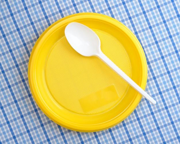 Пластиковая тарелка и ложка на столе