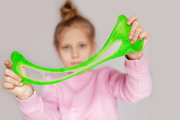 Милая девушка играет с зеленой слизью