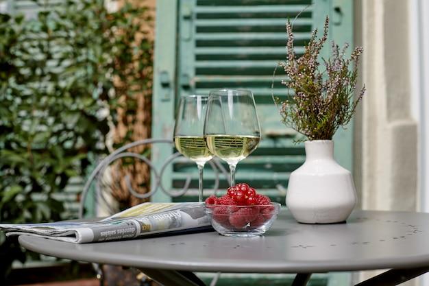 Белое вино, свежая малина и красная смородина на столе рядом с газетой и букет лаванды