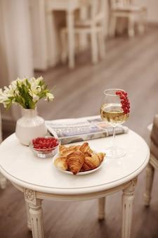 白ワイン、焼きたてのクロワッサン、新鮮な果実、白い花のつぼ