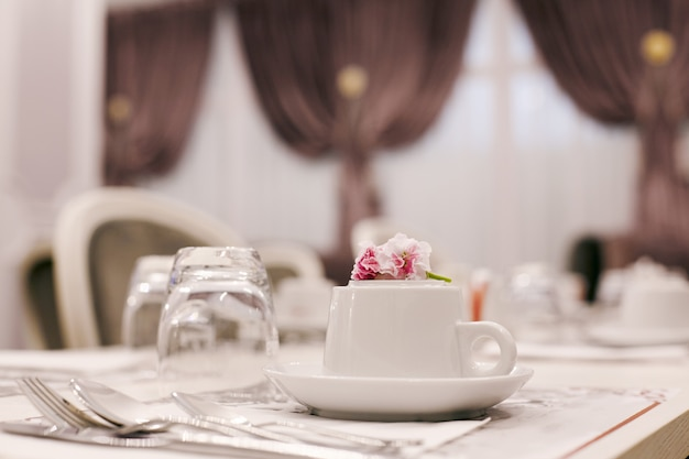 Завтрак в уютной столовой с керамическими чашками, бокалами и столовыми приборами на столе