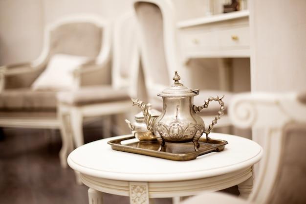 Серебряный старинный чайник и сахарница сидят на подносе на столе.
