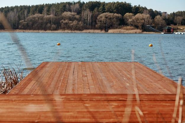 青い湖と春の森の海岸に茶色の木製の桟橋