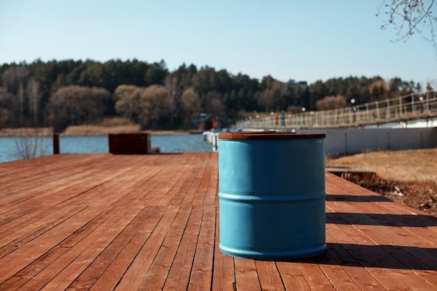 青い樽は木製の桟橋の湖の岸に立っています。春の風景です。