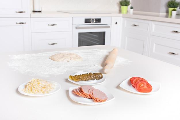 Тесто для пиццы и ингредиенты. тесто, помидоры, огурцы, сыр, салями