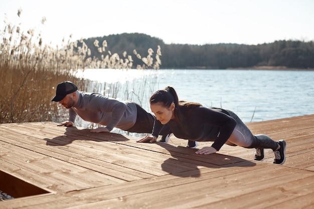 湖でスポーツをする少女と男。スポーツカップルが新鮮な空気の中で腕立て伏せを行います。スポーツ、フィットネス、ライフスタイル