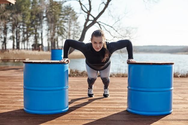 若い魅力的な女性が湖の桟橋で腕立て伏せを行います。女の子は新鮮な空気の中でスポーツに出かけます。スポーツ、フィットネス、ライフスタイル