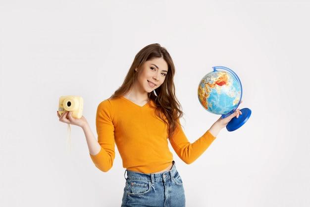 Красивая молодая девушка в желтом свитере держит глобус и камеру. отдых, путешествия, туризм. пространство для текста