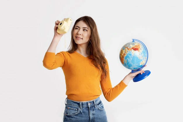 Симпатичная брюнетка в желтом свитере держит в руках глобус и смотрит в видоискатель камеры. отдых, путешествия, туризм. пространство для текста