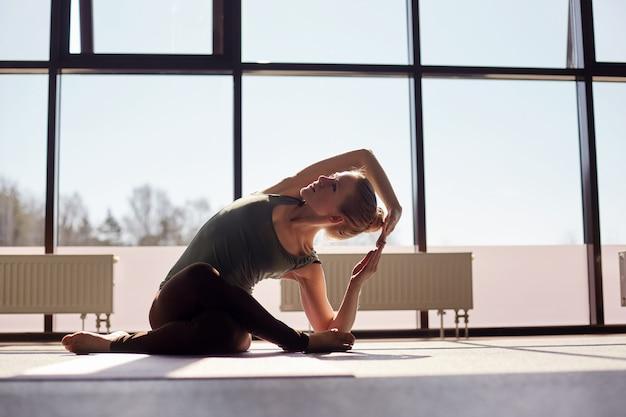Привлекательная девушка сидит, скрестив ноги, наклоняется и выполняет асану йоги. девушка занимается йогой в современной студии с панорамными окнами