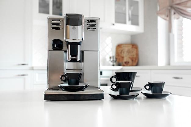 台所のテーブルの上のエスプレッソのカップとコーヒーマシン。閉じる