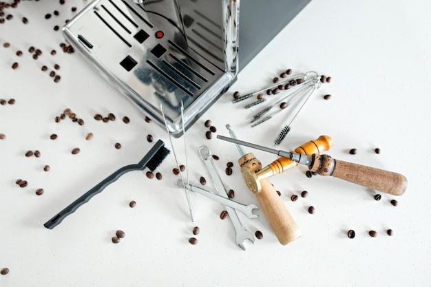 コーヒーマシンのクローズアップを修復するためのツール。コーヒー豆、木の板、コーヒーメーカー、キッチンテーブル