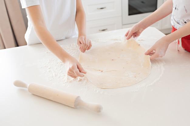 子供たちの手は、白いテーブルの上にピザ生地を広げます。台所で一緒に楽しんで。上からの眺め。