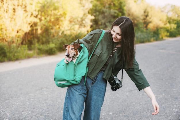 首にカメラを持った笑顔の女の子が、肩に緑のバックパックを抱えており、そこからかわいい犬が外を見ています。