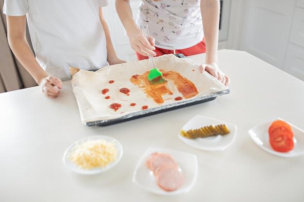 子供たちは家庭の台所でイタリアのピザを作ります。子供たちはケチャップで生地を塗ります。子供のコンセプトシェフ。ライフスタイル、率直な瞬間