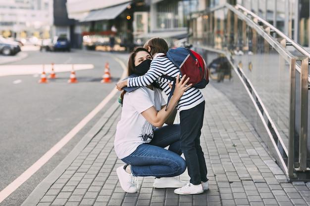 母と息子の屋外の防護マスクを着用