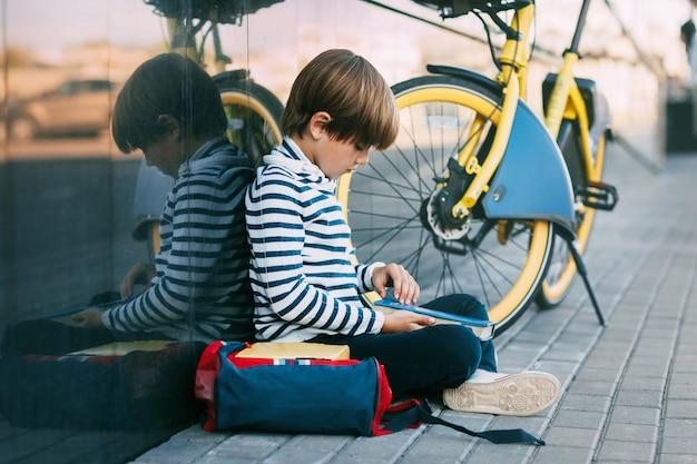 自転車の近くを読んでバックパックを持った少年