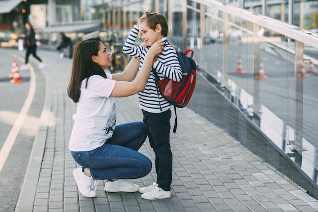 ママが男の子のセーターを屋外で調整