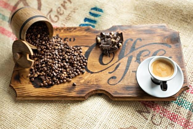 散在のコーヒー豆、エスプレッソのカップ、木の板にナッツ入りのチョコレートのかけら。