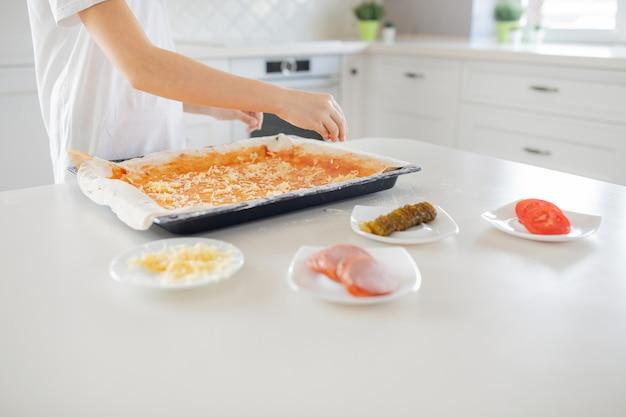 Концепция приготовления - готовьте вручную добавление тертого сыра в пиццу на домашней кухне. крупный план