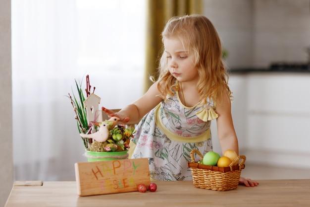 子供はイースターエッグのバスケットと一緒に休日テーブルに座っています。