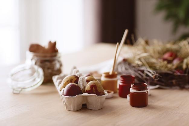 Пасхальные яйца, печенье, краски, кисти на столе. вид сбоку
