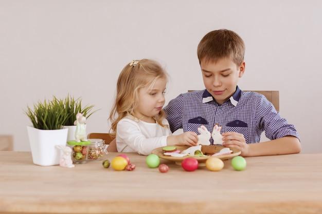 兄と女の子が休日のテーブルに座っているとクッキーとイースターエッグを広げている