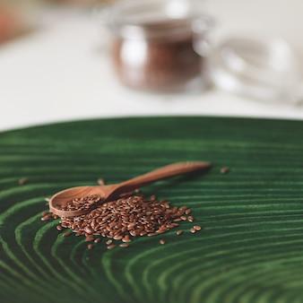 木のスプーンでの亜麻の種子の健康的な栄養。有機ビーガンフードのクローズアップ。