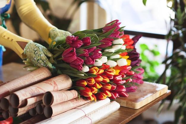 女の子はペーパークラフトのチューリップのカラフルな花束を詰める