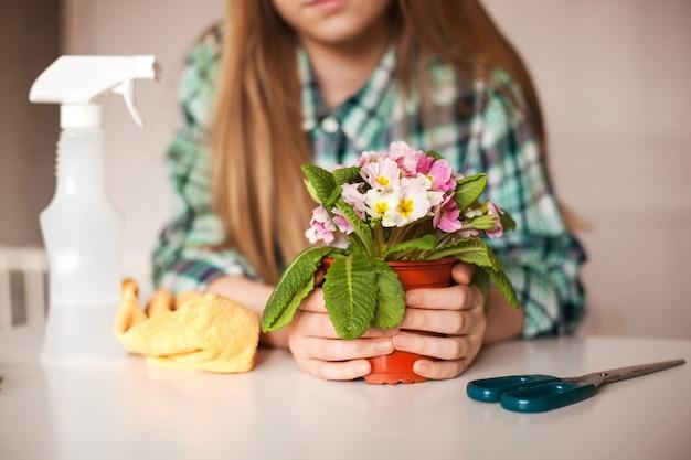 Девушка ухаживает за растениями в своем доме, крупный план