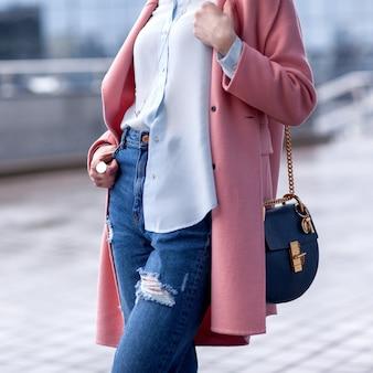 ピンクのコートを着て通りを歩いてスタイリッシュな女性。