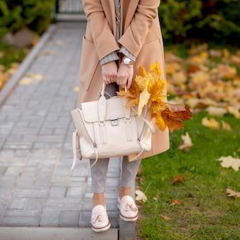 スタイリッシュな女の子がベージュのコートと帽子で秋の公園で歩く
